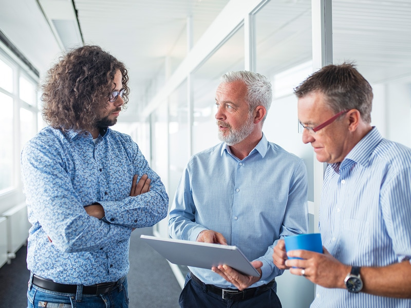 Die Abteilung Entwicklung und Architektur bei einem kurzen Meeting auf dem Flur