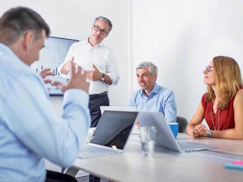 Flache Hierarchien: Meeting-Teilnehmer diskutieren auf Augenhöhe